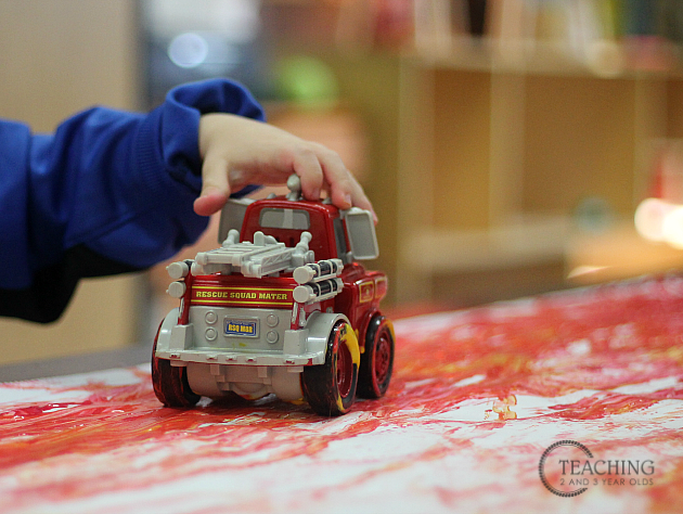toddler painting with firetrucks
