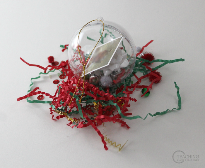 This toddler and preschool keepsake ornament is fun because it allows the children to choose what small items they want to put into their plastic ornament, along with a laminated photo of themselves. It is then wrapped and sent home before winter break.